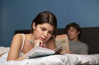 Young woman writing diary in bed, man in the background, selective focus