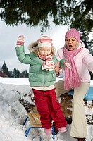 Mother and daughter playing in snow