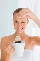 Young woman holding tea bag