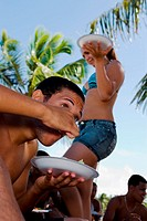 Young man eating at beach party
