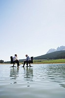 Businessman and woman in office chairs on water talking