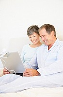 a senior couple using a laptop sitting in bed