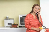 Portrait of a young woman using a telephone in the kitchen