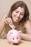 Close-up of a young woman inserting money into a piggy bank