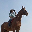 Low angle view of a teenage girl riding a horse and looking through a pair of binoculars