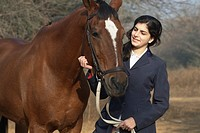 Close-up of a teenage girl standing with a horse and smiling