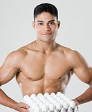 Portrait of a young man holding a carton of eggs