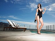 Woman in bathing suit standing with champagne at outdoor pool