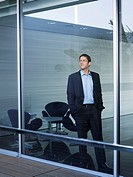 Young businessman standing at window in office