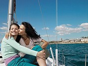 Mature mother kissing daughter on yacht, smiling