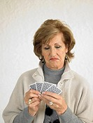Senior woman playing cards, pulling face
