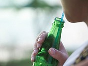 Young woman holding bottle using drinking straw mid section