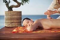 Woman receiving oceanside massage