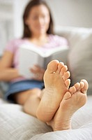 Woman with bare feet reading on couch