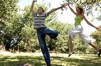 Side profile of a mid adult woman and her son jumping in a park