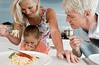 Senior couple trying to feed their granddaughter
