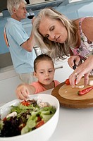 Senior woman and her granddaughter preparing salad with a senior man drinking wine in the background