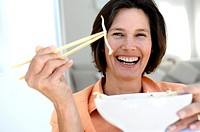 Portrait of a mature woman holding bean sprouts with a pair of chopsticks and smiling