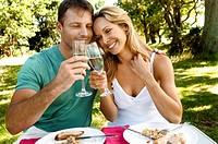Mid adult couple toasting with champagne flutes and smiling