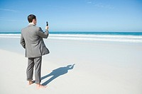 Barefoot businessman standing on beach, holding up cell phone