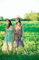 Young hippie women standing in field, looking away, full length