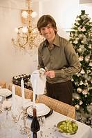 Man setting ornate dinner table