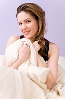 Woman holding blankets over herself in bed