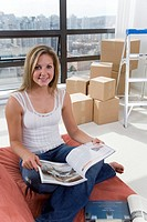 Woman reading on sofa with moving boxes in corner