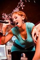 Woman wearing crown signing at karaoke bar