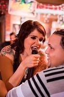 Young woman with tatoos singing at bar