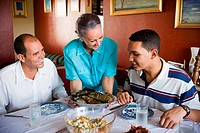 Mature couple and their son sitting at the dining table