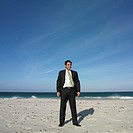Hispanic businessman standing on beach