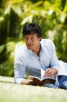 South American man reading in grass