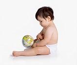 Studio shot of Hispanic baby holding globe