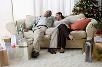 Hispanic couple sleeping on sofa on Christmas