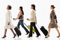 Multi-ethnic businesswomen pulling suitcases