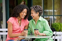 African American mother and adult daughter laughing