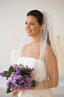 Hispanic bride holding bouquet of flowers