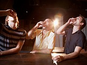 Hispanic men drinking shots at bar
