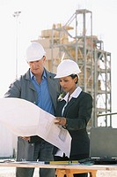 Building contractors holding blueprint