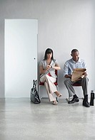 Young man and woman waiting on chairs in corridor