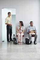 Three people waiting in corridor one man talking to woman