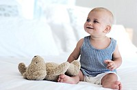 Baby sitting with teddy bear, indoors