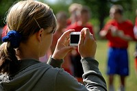 Girls Using Digital Camera Outdoors to Take Picture Soccer Players