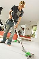 Teenager vacuuming, indoors