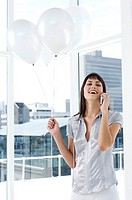 Young smiling woman phoning, holding white balloons