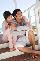 Smiling couple sitting on wooden terrace