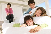 Smiling couple and two children on bed