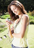 A young woman listening to music outdoors