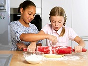 Two girls rolling out biscuit dough